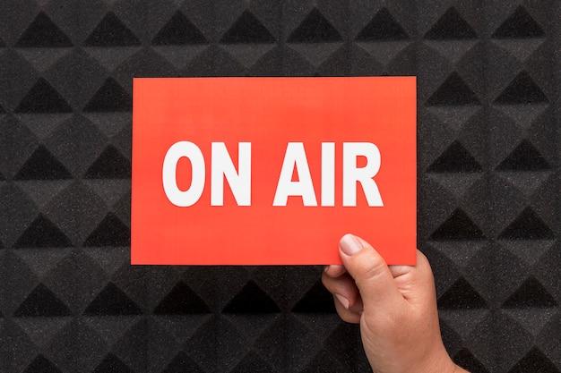 Persoon die op lucht live streaming radiobanner houdt Premium Foto