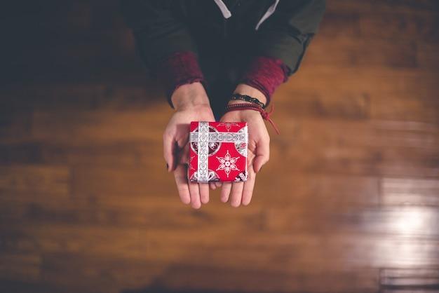 Persoon die rode en witte doos houdt Gratis Foto
