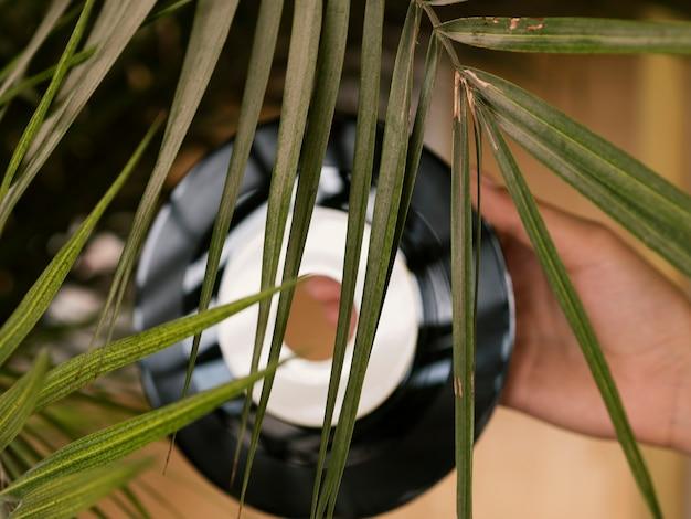 Persoon die vinylverslag achter een blad houdt Gratis Foto