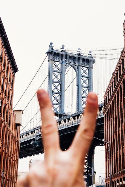 Persoon die vredesteken op brugachtergrond toont Gratis Foto