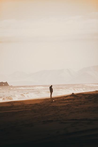 Persoon die zich op het zandstrand met een heldere witte hemel Gratis Foto