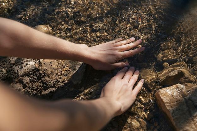 Persoon dompelen handen in water Gratis Foto