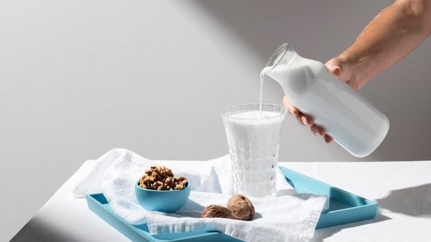 Persoon gieten melk in vol glas met walnoten op dienblad Gratis Foto