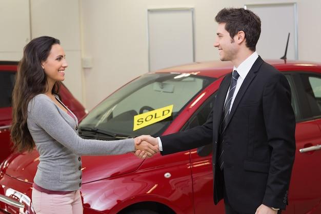Persoon handen schudden voor een verkochte auto Premium Foto