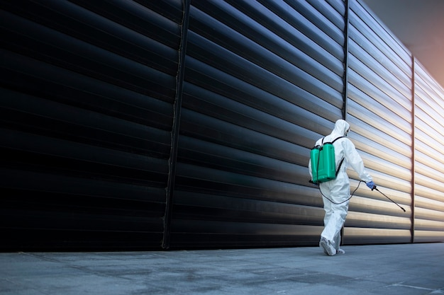 Persoon in wit chemisch beschermingspak die openbare ruimtes desinfecteert om de verspreiding van het zeer besmettelijke coronavirus te stoppen Gratis Foto