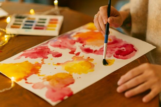 Persoon met behulp van kwast op abstracte schilderkunst Premium Foto