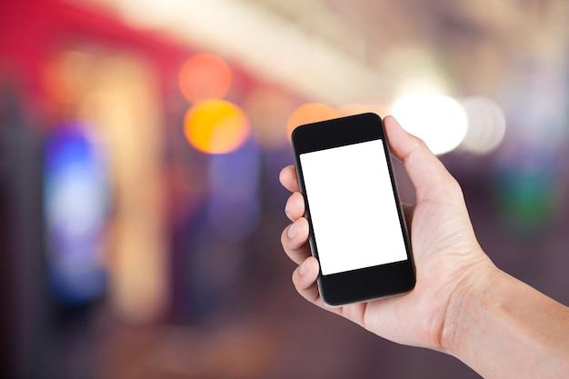 Persoon met behulp van smartphone witte scherm houder bij de hand met wazige achtergrond van mensen lopen in het elektrische treinstation. Premium Foto