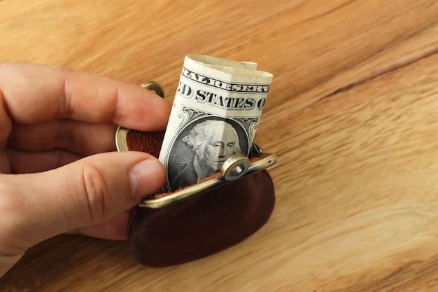 Persoon met een portemonnee met wat geld erin boven een houten oppervlak Gratis Foto