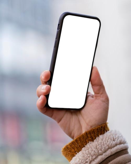 Persoon met een smartphone met een leeg scherm Premium Foto