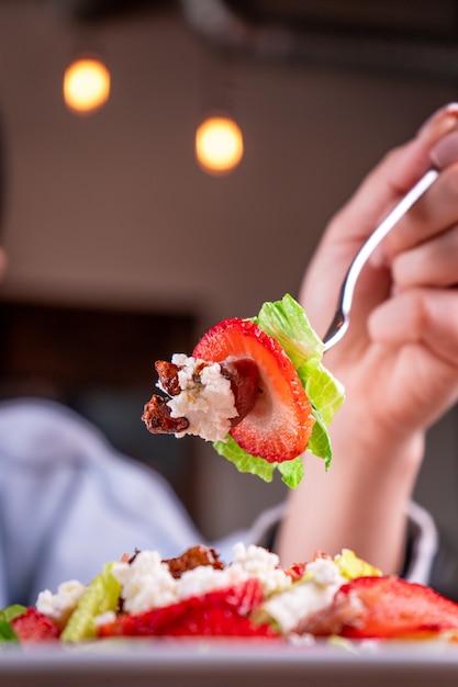 Persoon met een vork die een deel van de salade van groenten en fruit vasthoudt Gratis Foto