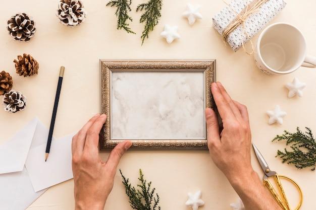 Persoon met frame op beige tafel Gratis Foto