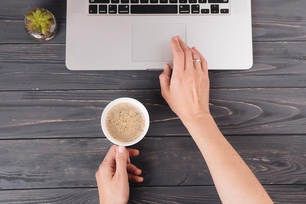 Persoon met koffie die aan laptop bij lijst werkt Gratis Foto