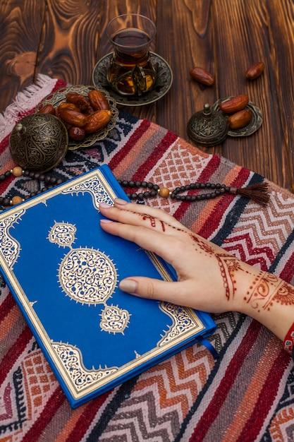 Persoon met mehndi die de koran vasthoudt bij thee en datafruit Gratis Foto