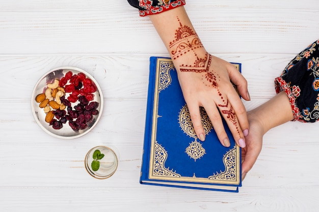 Persoon met mehndi die de koran vasthoudt in de buurt van gedroogd fruit Gratis Foto