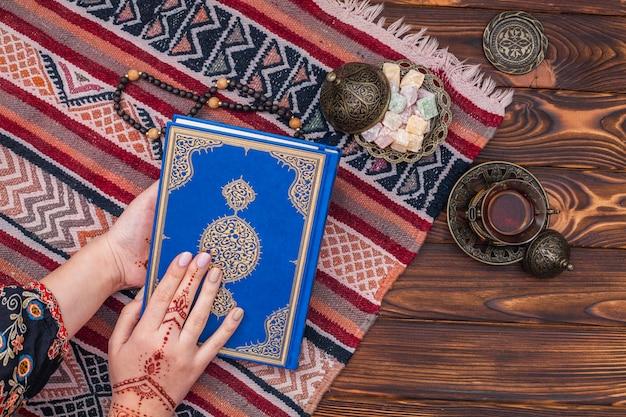 Persoon met mehndi die de koran vasthoudt in de buurt van turks genot Premium Foto