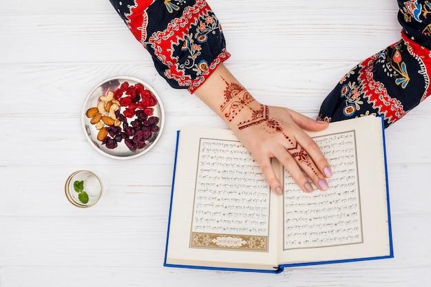 Persoon met mehndi die koran dichtbij droog fruit leest Gratis Foto