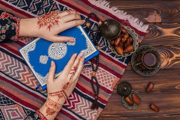 Persoon met mehndi die koranboek houdt dichtbij theekop Gratis Foto