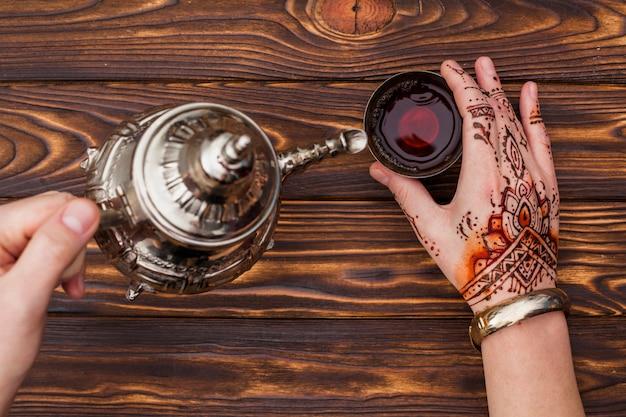 Persoon met mehndi die thee in kleine kop giet Gratis Foto