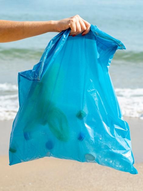 Persoon met vuilniszak met recyclebare plastic fles Gratis Foto