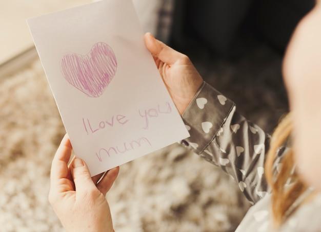 Persoon met wenskaart met ik hou van je moeder inscriptie Gratis Foto