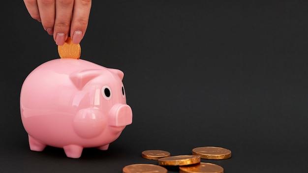Persoon roze spaarvarken munten aanbrengend Gratis Foto