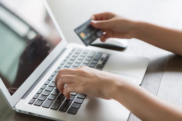 Persoon schrijven op een laptop en een credit card Gratis Foto