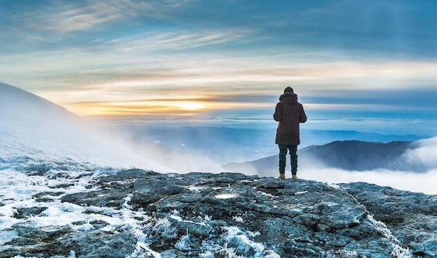 Persoon staat op een met sneeuw bedekte klif boven het adembenemende uitzicht op de bergen onder de zonsondergang Gratis Foto