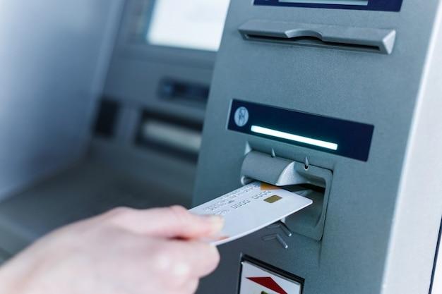 Persoon steek kaart in automatische geldautomaat. Premium Foto