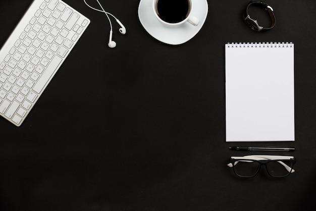 Persoonlijke accessoires; koffiekop; oortelefoon; brillen en toetsenbord op zwarte achtergrond Gratis Foto