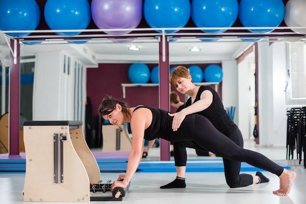 Persoonlijke instructeur die jonge vrouw controleren die op combo wunda pilates stoel uitoefenen Premium Foto