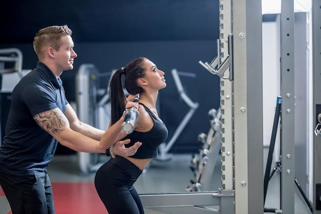 Persoonlijke trainer die een jonge vrouw helpt een barbell op te heffen terwijl het uitwerken in een gymnastiek Premium Foto