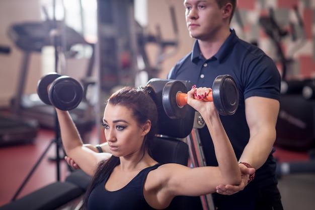 Persoonlijke trainer die vrouw helpt die met zware domoren werkt Premium Foto