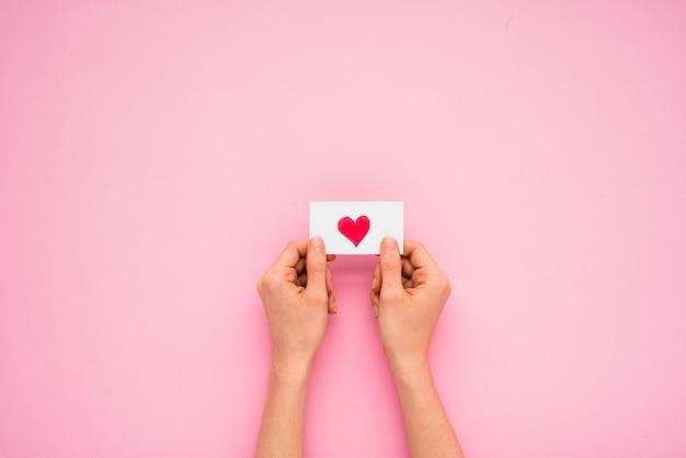 Persoonshanden die document met hartsymbool houden Gratis Foto
