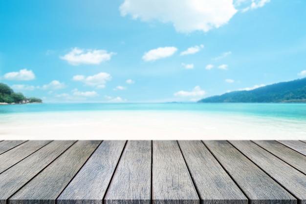 Perspectief houten tafel bovenop vervagen zee op zonnige dag achtergrond. Premium Foto
