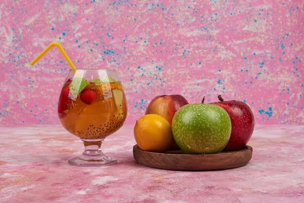 Perzik, lemonnd appels met kopjes sap op een houten bord in het midden. Gratis Foto