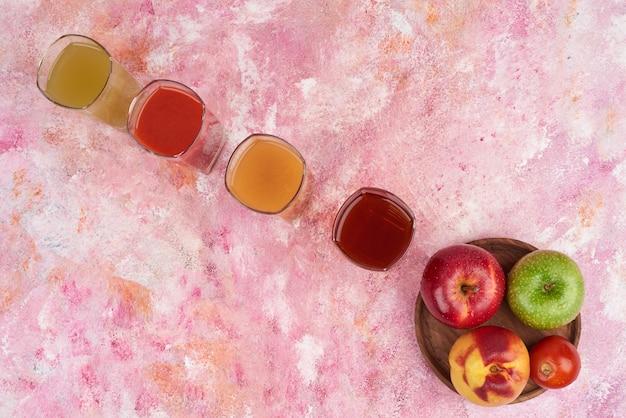 Perzik, lemonnd appels met kopjes sap op een houten bord. Gratis Foto