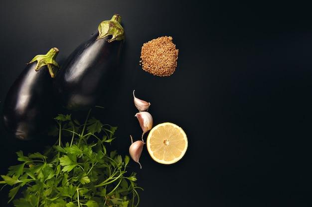 Peterselie, knoflook, citroen, sesamzaadjes en twee verse aubergines die op zwart worden geïsoleerd Gratis Foto