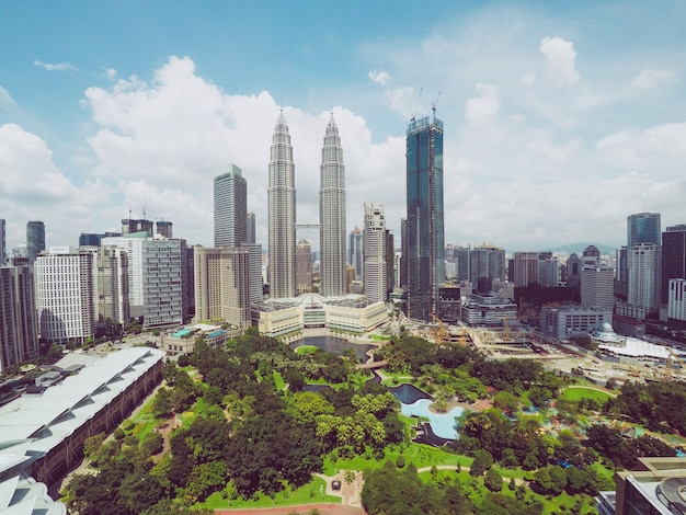 Petronas twin towers in de buurt van wolkenkrabbers en bomen onder een blauwe hemel in kuala lumpur, maleisië Gratis Foto