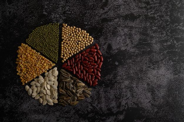 Peulvruchten gerangschikt in een cirkel op de zwarte cementvloer. Gratis Foto