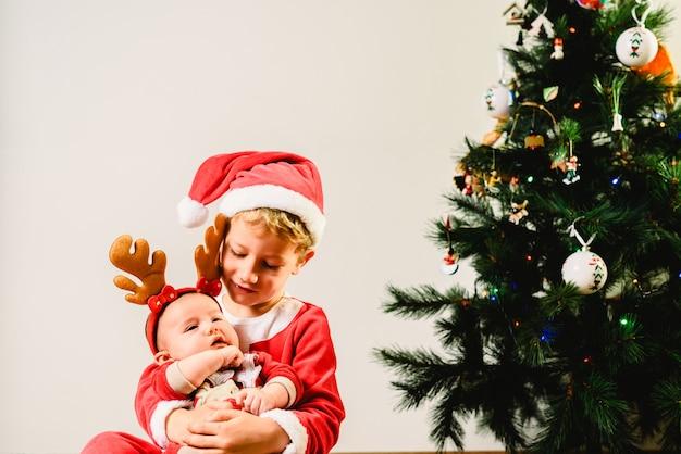 Peuter en pasgeboren die baby, siblings als kerstmis, vakantieconcept worden vermomd Premium Foto