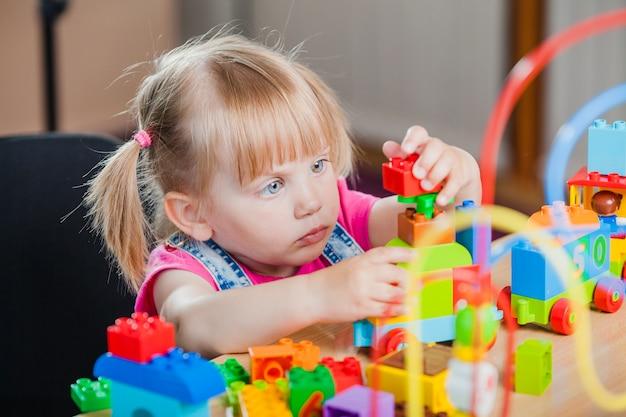 Peuter meisje met kleurrijk speelgoed Premium Foto