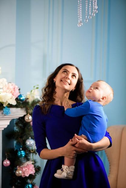 Peuter met moeder in de feestelijk ingerichte kamer met kerstboom. Premium Foto