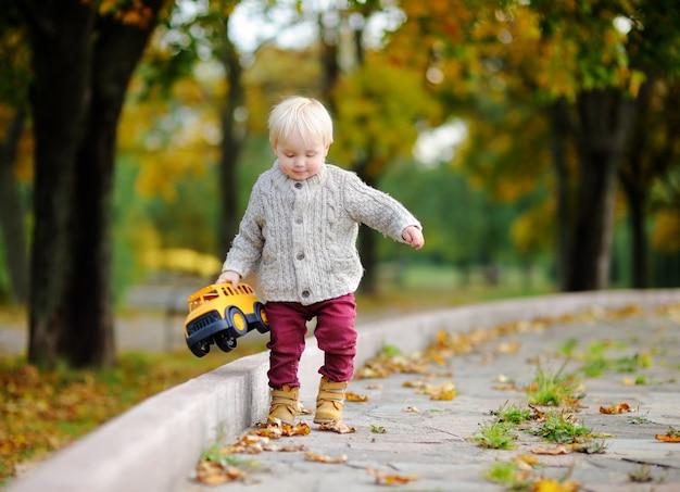 Peuter met plezier in herfst park. weinig jongen die met stuk speelgoed auto in openlucht speelt Premium Foto