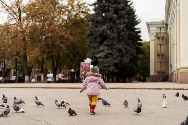 Peutermeisje die in regenlaarzen met vogels op stadsvierkant spelen. buitenshuis jeugd activiteit Premium Foto