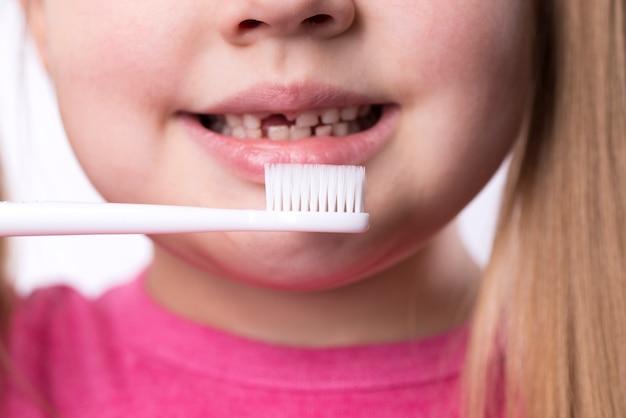 Peutermeisje met eerste volwassen snijtanden en een tandenborstel Premium Foto