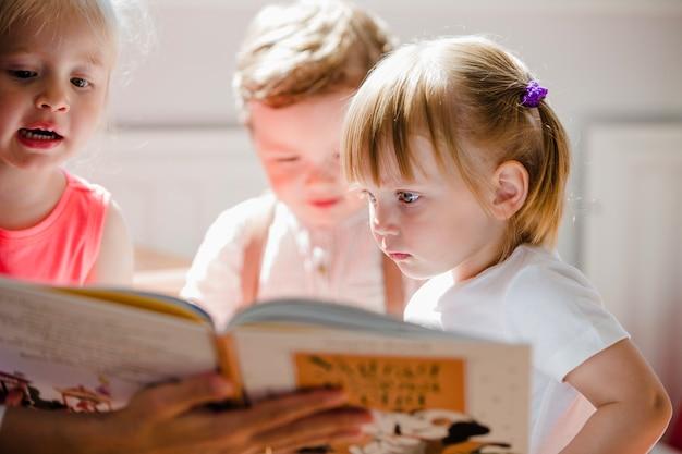 Peuters lezen boek in de kleuterschool Gratis Foto