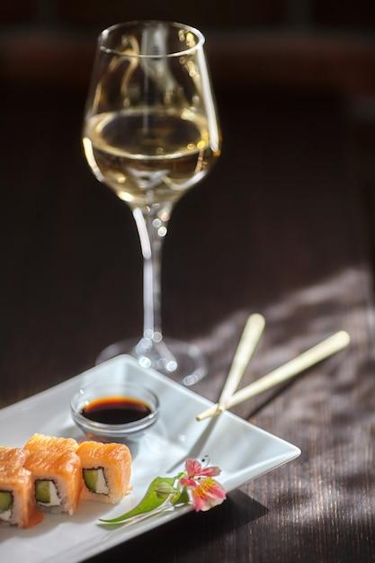 Philadelphia makisushi rolt met zalm, kaasroom, komkommer op witte plaat en glas wijn Premium Foto