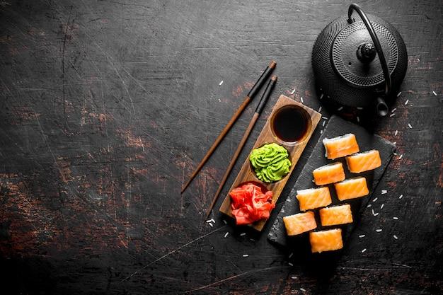 Philadelphia sushi roll op een stenen tribune met gember, wasabi en sojasaus op zwarte rustieke tafel Premium Foto