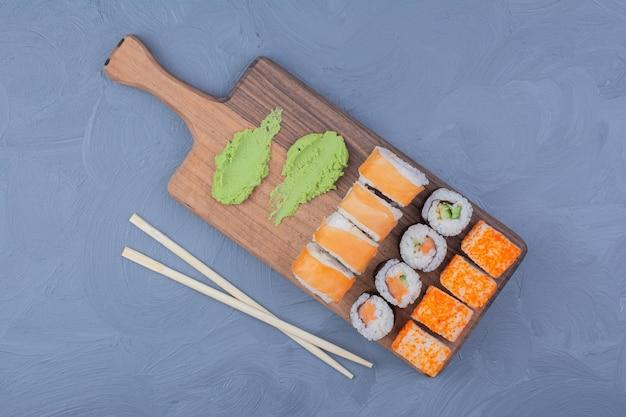 Philadelphia, zalm en sake makibroodjes met wasabi op een houten schotel. Gratis Foto