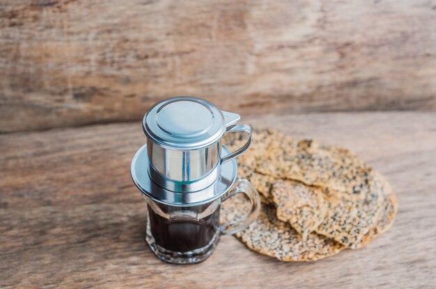 'phin' traditioneel vietnamees koffiezetapparaat, plaats op het glas, voeg gemalen koffie toe, giet er heet water in en wacht tot de koffie in het glas druppelt. Premium Foto